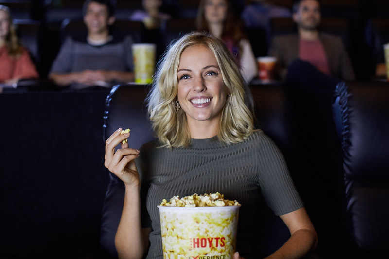 Women smiling and eating popcorn whilst watching a movie at the HOYTS cinema in EntX